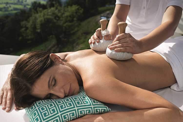 Kräuterstempel Massage im Freien als Wellness Highlight